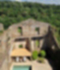 Terrasse aménagée dans ruines antiques sur fond de forêt